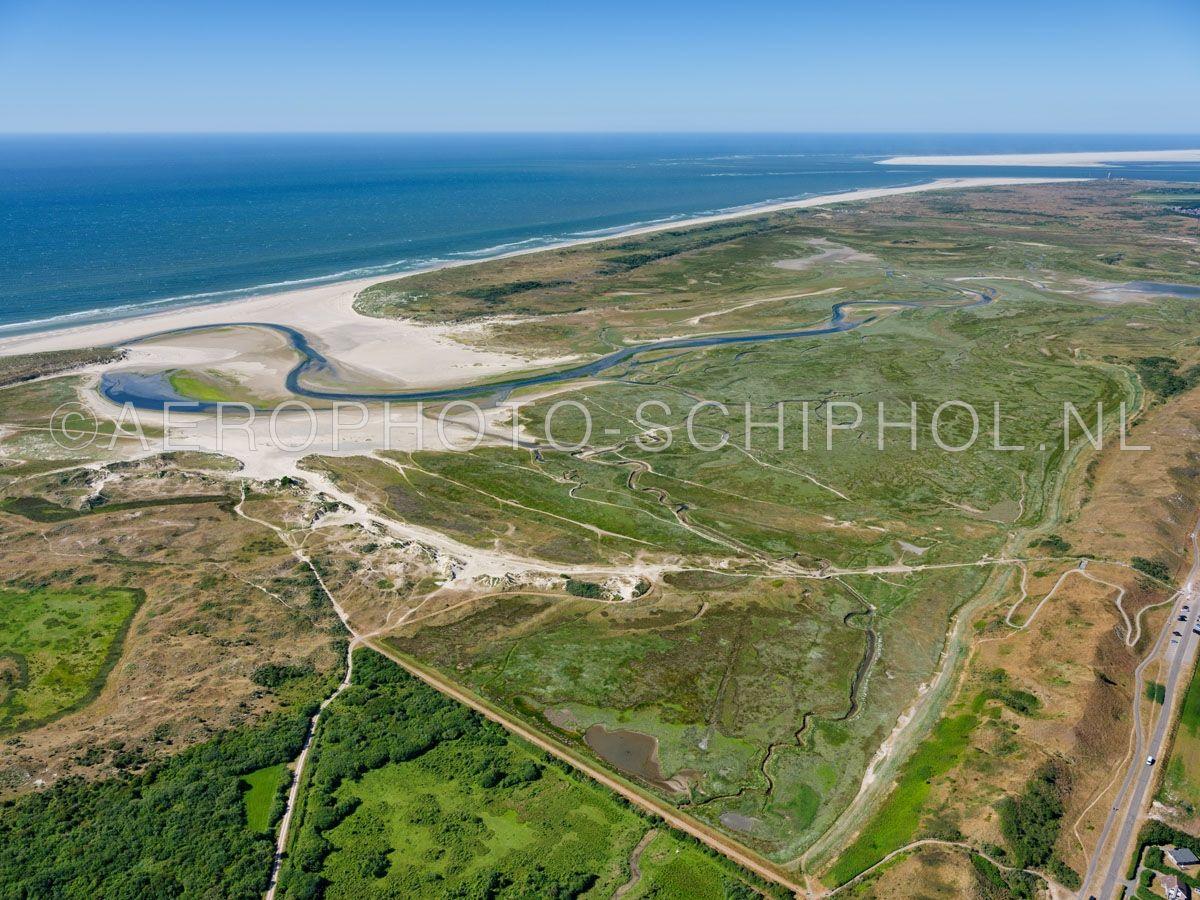 luchtfoto |  Texel, de Slufter mret rechts de Zanddijk. De Slufter is een standvlakte en kwelderlandschap tussen de duinen met een open verbinding naar de Noordzee. opn. 30/06/2018