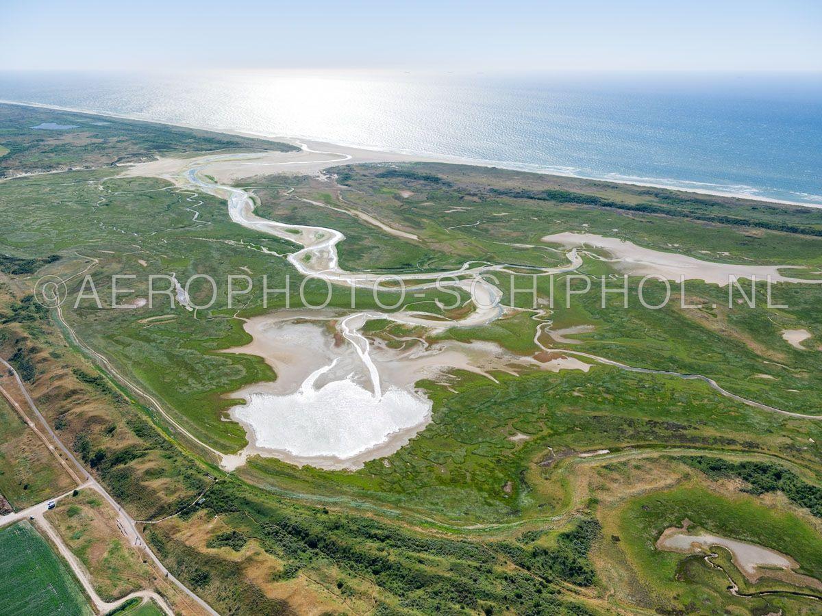 luchtfoto    Texel, de Slufter en de Noorzeekust gezien vanuit het Noordoosten. De Slufter is een kwelderlandschap, een standvlakte tussen de duinen met een open verbinding naar de Noordzee. opn. 30/06/2018